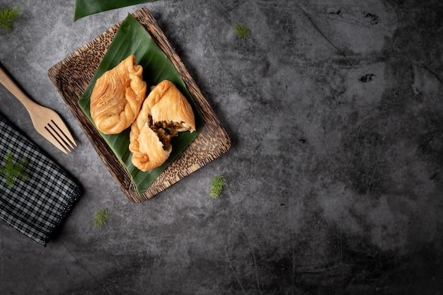Pollo al curry, spuntino tailandese tradizionale su sfondo nero
