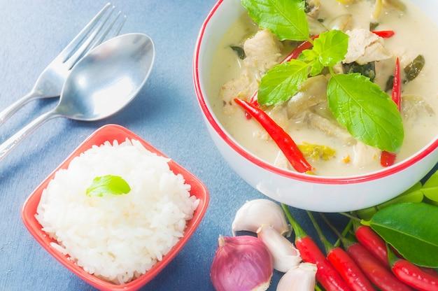 Pollo al curry verde con ingrediente piccante crudo e riso con cucchiaio e forchetta