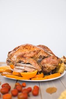 Pollo al forno con le arance sul fondo bianco della parete