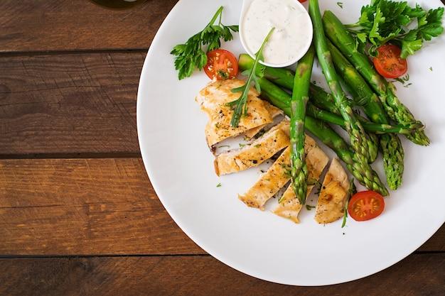 Pollo al forno guarnito con asparagi e pomodori.
