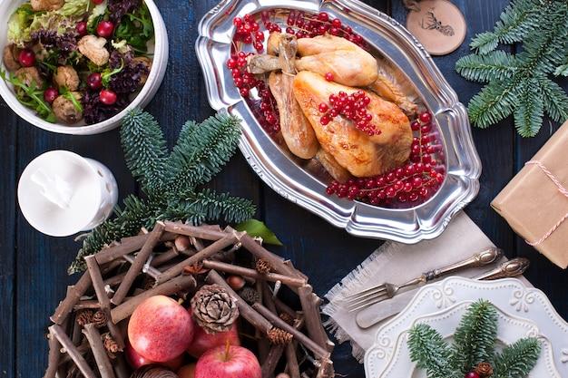 Pollo al forno su un piatto con bacche rosse. su un tavolo di legno blu con un rastrello
