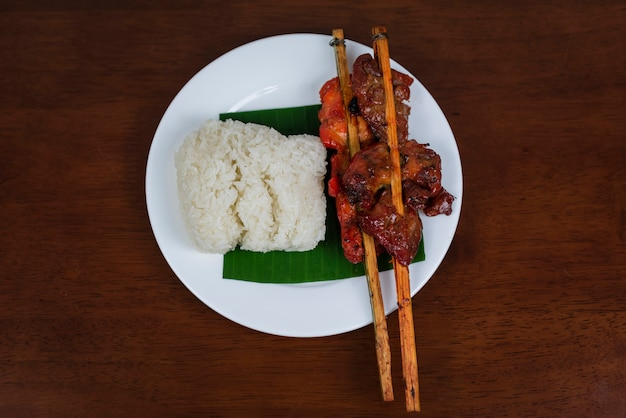Pollo alla griglia con riso appiccicoso sulla foglia di banana e fondo in legno