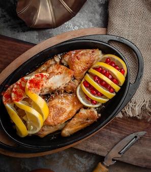 Pollo alla griglia con semi di limone e melograno all'interno della padella di ferro nero.