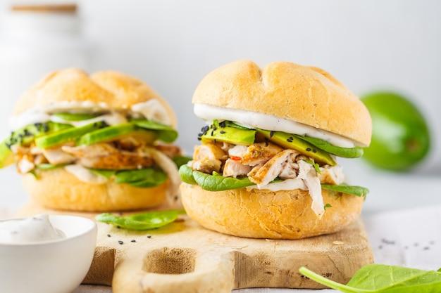 Pollo alla griglia e hamburger di avocado su tavola di legno.