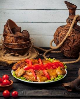 Pollo alla griglia guarnito con fettine di pomodoro su foglie di lattuga