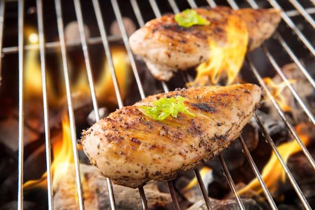 Pollo alla griglia marinato sulla griglia fiammeggiante