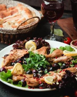 Pollo alla griglia servito con erbe verdi e fette di limone.