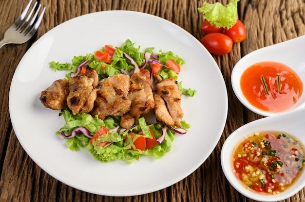 Pollo alla griglia su un piatto bianco con insalata di pomodori, carote e peperoncini tagliati a pezzi.