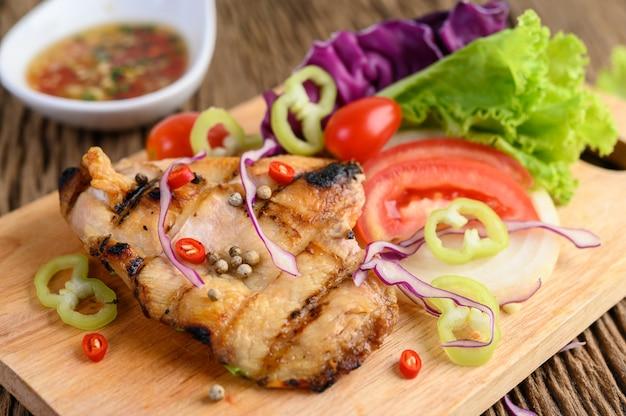 Pollo alla griglia su un tagliere di legno con insalata, pomodori, peperoncini tagliati a pezzi e salsa.