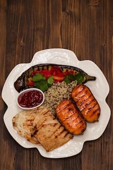 Pollo arrostito con le verdure e la salsa sul piatto bianco