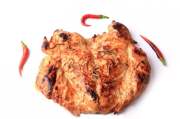 Pollo arrostito con rosmarino e primo piano rosso del peperoncino isolati