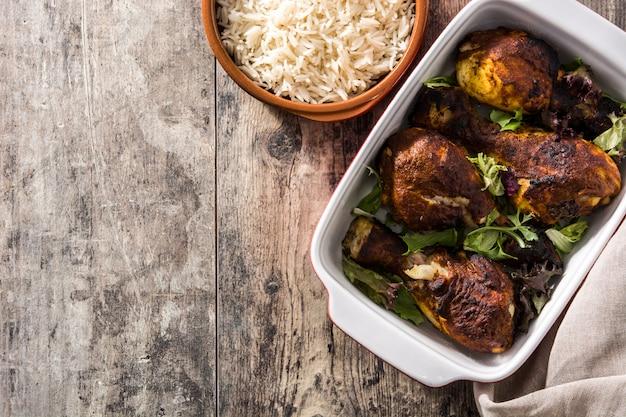 Pollo arrostito di tandoori con riso basmati sulla tavola di legno. vista dall'alto.