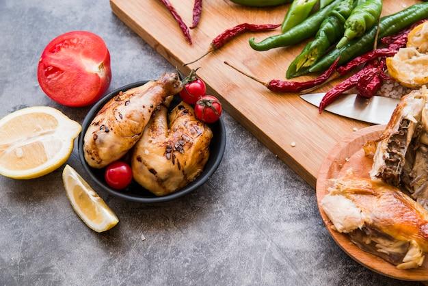 Pollo arrosto con peperoncino e pomodoro su sfondo concreto