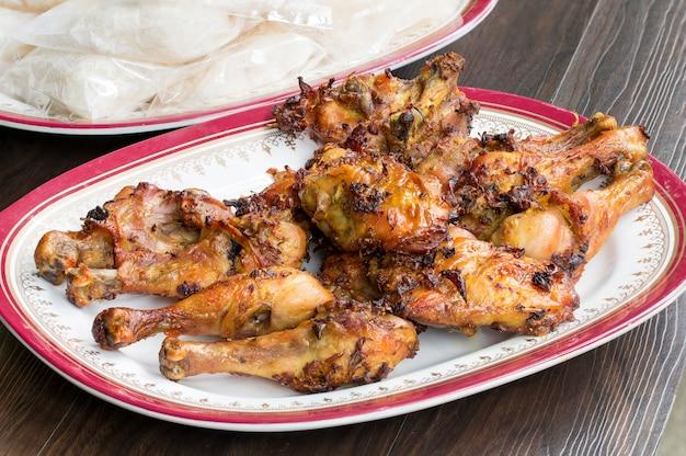 Pollo arrosto e riso appiccicoso con piatto su legno.
