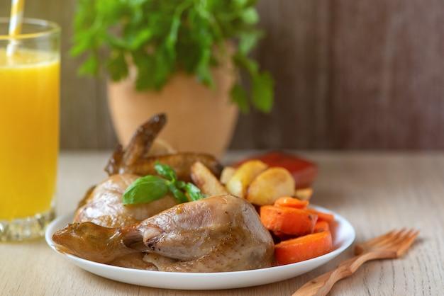Pollo arrosto, patate e verdure in zolla bianca su fondo di legno