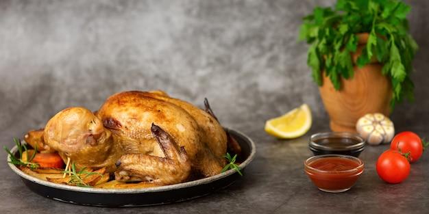 Pollo arrosto, patate e verdure nel piatto su sfondo grigio. vista laterale