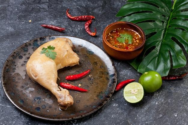 Pollo bollito con salsa di pesce in piatto su roccia nera