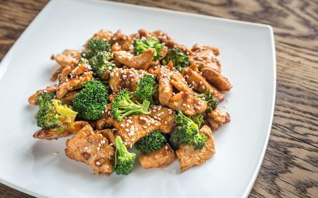 Pollo con broccoli su un piatto bianco