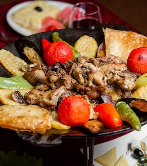 Pollo con fette di patate e pomodoro e pepe grigliati