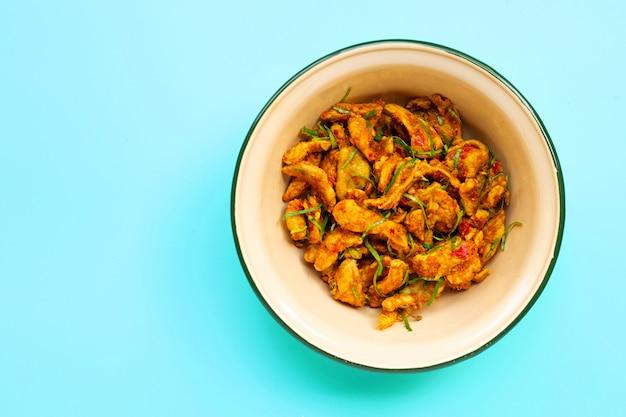 Pollo con pasta di curry gialla su fondo blu. copia spazio