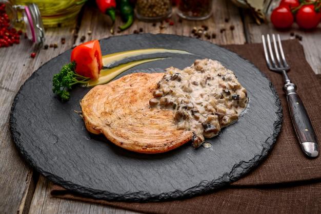 Pollo cremoso del fungo all'aglio sulla tavola di legno