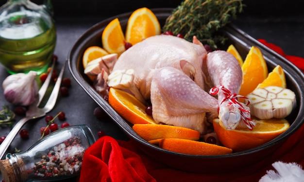 Pollo crudo con arance e mirtilli rossi per natale. cena del ringraziamento. messa a fuoco selettiva.
