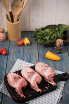 Pollo crudo del primo piano sul bordo di legno con i peperoni