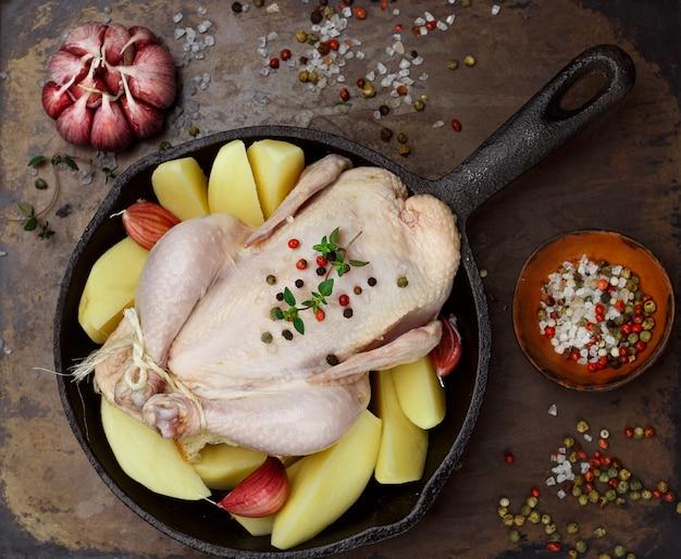 Pollo crudo intero con patate, aglio, timo e spezie