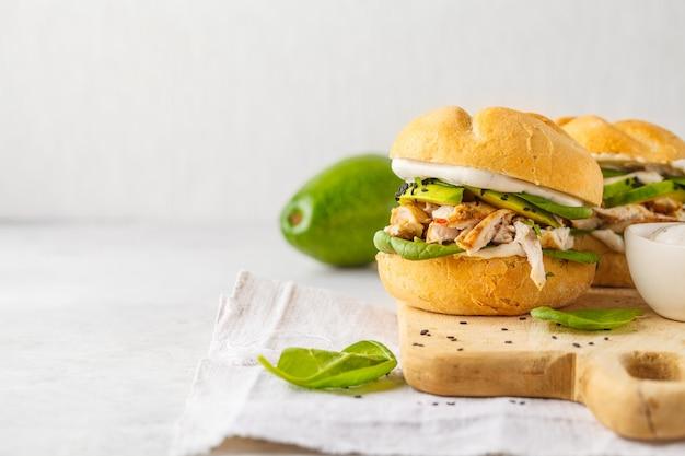 Pollo e avocado hamburger alla griglia sul bordo di legno, spazio della copia.