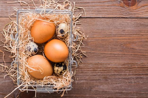 Pollo e uova di quaglia in un cesto con vista dall'alto di strawin