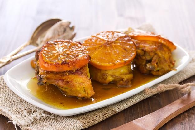 Pollo fritto con l'arancia sul piatto bianco su legno
