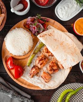 Pollo fritto con lavash e riso su un vassoio di legno