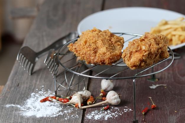 Pollo fritto con le patate fritte sulla tavola di legno.