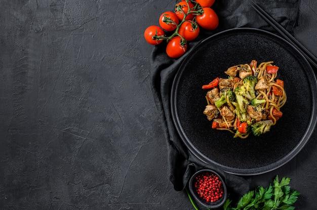 Pollo fritto con salsa di soia di verdure, wok. cibo asiatico tradizionale. tavolo in pietra nera