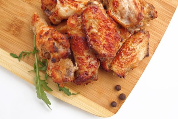 Pollo fritto cotto, con una crosta dorata su una tavola di legno su un bianco