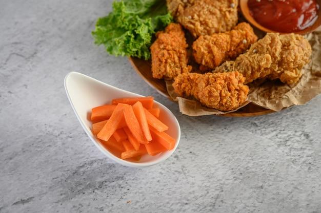 Pollo fritto croccante su un piatto con salsa al pomodoro e carota