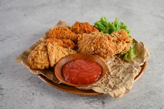 Pollo fritto croccante su un piatto con salsa al pomodoro