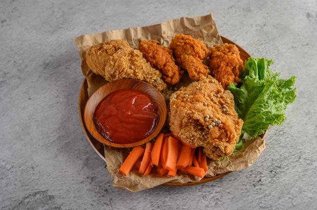 Pollo fritto croccante su un piatto di legno con salsa al pomodoro e carota