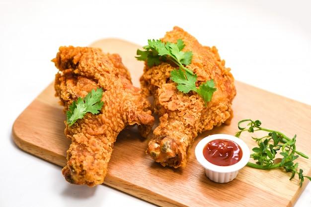 Pollo fritto croccante sul bordo di legno del piatto con ketchup