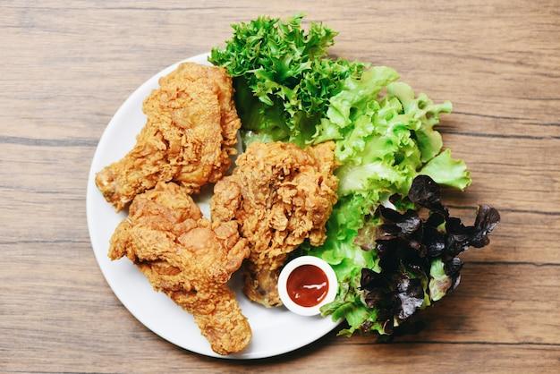 Pollo fritto croccante sul piatto bianco con ketchup e insalata lattuga vegetale su legno