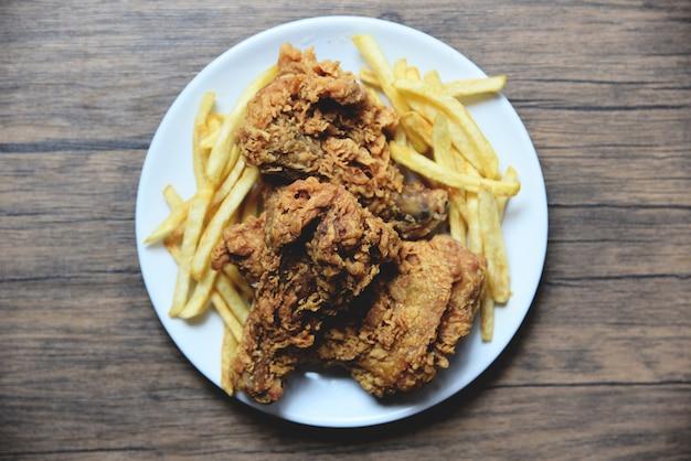 Pollo fritto croccante sul piatto bianco con patatine fritte sul tavolo da pranzo
