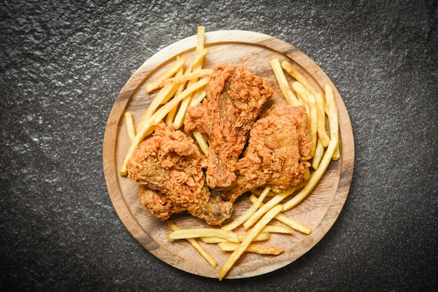 Pollo fritto croccante sul vassoio in legno con patatine fritte su oscurità