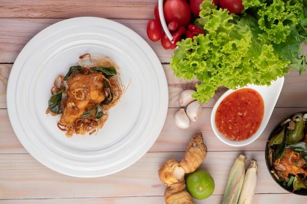 Pollo fritto dell'erba su un piatto bianco su un pavimento di legno.