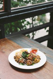 Pollo fritto delle cosce di mescolanza di stile tailandese con sale e peperoncino rosso.