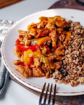 Pollo fritto di vista frontale affettato con grano saraceno dentro il piatto bianco sul pavimento leggero