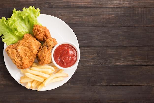 Pollo fritto, ketchup e patatine fritte su fondo di legno. fast food