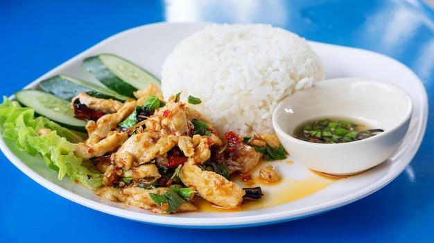 Pollo fritto piccante con foglie di basilico e riso al vapore.