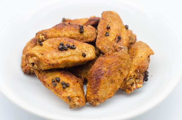 Pollo fritto sul piatto bianco con fondo bianco, alimento dell'asia, alimento non sano