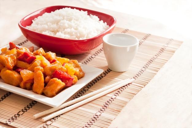 Pollo in agrodolce con peperone e ananas. riso bianco in superficie. copia spazio