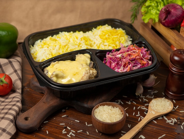 Pollo in crema di salsa di formaggio fuso con contorno di riso e insalata di carote di cavolo